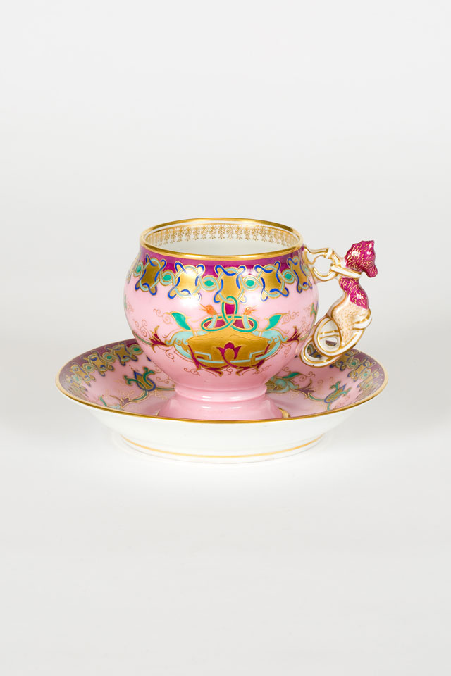 Cup and saucer with intricate enamelled and gold scroll work on a pink ground, Kornilov Factory