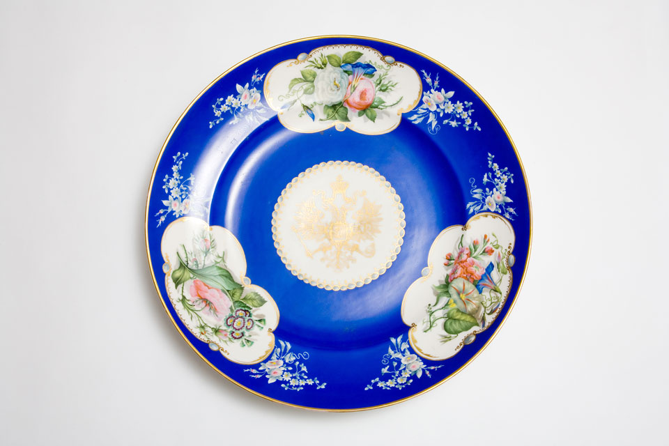 Large, circular Popov porcelain dish with gilt Russian eagle and three panels of flowers on a blue ground